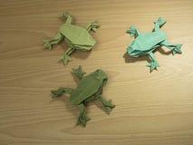 在木背景的三Origami青蛙 免版税库存图片