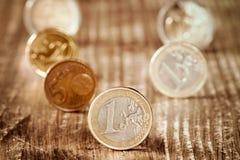 在木背景的不同的欧洲硬币 免版税库存照片