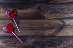 在木背景的两个心形的棒棒糖 免版税库存照片