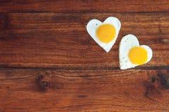 在木背景的两个心形的煎蛋 免版税图库摄影