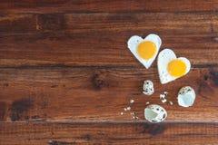 在木背景的两个心形的煎蛋 免版税库存照片