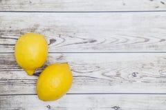 在木背景的两个新鲜的黄色柠檬 库存照片