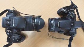 在木背景的两台照相机 免版税库存图片
