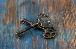 在木背景的两把老钥匙 库存照片