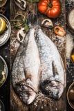 在木背景的两条未加工的dorado鱼与烹调成份,顶视图 海鲜 免版税库存照片