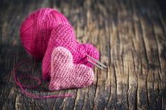 在木背景的两钩针编织桃红色心脏 免版税库存图片