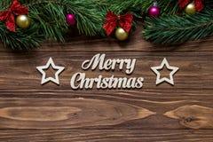 在木背景的中心和两个美丽的星的圣诞快乐标题与杉树在上面分支 库存图片