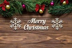 在木背景的中心的圣诞快乐与杉树的在上面分支屏幕和两个 免版税库存照片