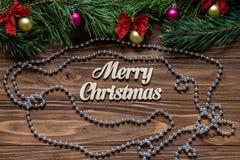 在木背景的中心的圣诞快乐标题与闪亮金属片和一个银色花冠的 免版税库存照片