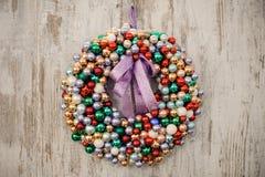 在木背景的五颜六色的圣诞节花圈装饰中看不中用的物品 库存照片
