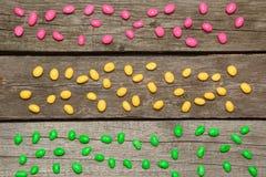 在木背景的五颜六色的甜糖果 平的位置 顶视图 装饰 免版税库存图片