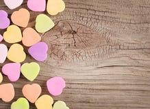 在木背景的五颜六色的糖果心脏 免版税图库摄影