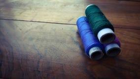 在木背景的五颜六色的缝合针线 免版税库存照片