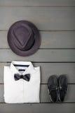 在木背景的人的成套装备 孩子时尚衣裳 灰色浅顶软呢帽、白色衬衣、黑蝶形领结和小船鞋子男孩的 免版税库存照片