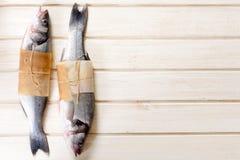 在木背景的低音鱼 库存图片