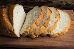 在木背景的切的面包 免版税图库摄影