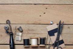 在木背景的刺绣和针线工具 免版税库存图片