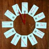 在木背景的十二张圣诞节愿望卡片 等待的圣诞节时钟  库存照片