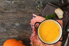 在木背景的南瓜奶油色汤碗 免版税图库摄影