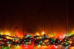 在木背景的发光的圣诞节诗歌选在黑暗中 免版税库存照片