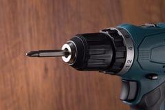 在木背景的可再充电的电螺丝刀 修理和工艺品 免版税库存图片