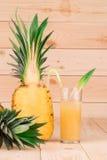 在木背景的可口菠萝汁 库存图片
