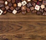 在木背景的各种各样的巧克力 库存照片