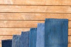 在木背景的各种各样的蓝色牛仔裤 顶视图 免版税库存图片