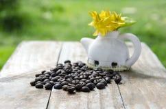 在木背景的咖啡豆与ixora开花 免版税库存图片