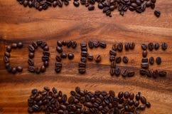 在木背景的咖啡豆英国字符 库存照片