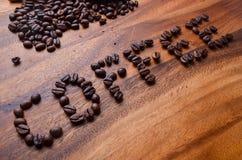 在木背景的咖啡豆英国字符 库存图片