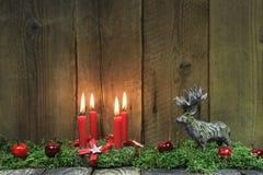 在木背景的四个红色灼烧的圣诞节蜡烛与鹿 库存图片