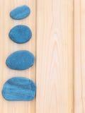 在木背景的四块板岩石头 免版税库存图片