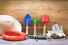 在木背景的园艺工具与钳子草帽,绳索,手套修平刀园艺设备 免版税库存照片