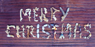 在木背景的圣诞快乐珊瑚题字 免版税库存照片
