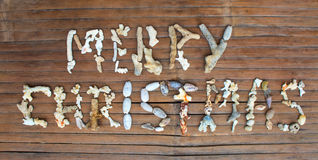 在木背景的圣诞快乐珊瑚题字 库存图片