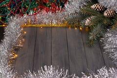 在木背景的圣诞灯与自由空间 与银色圣诞节链子的框架 免版税图库摄影