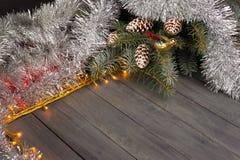 在木背景的圣诞灯与自由空间 与银色圣诞节链子的框架 免版税库存图片