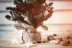 在木背景的圣诞节冷杉木与光以一张新年明信片的设计的星形式 火光拷贝空间 免版税库存照片