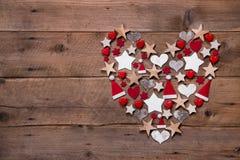 在木背景的圣诞节心脏与另外装饰 免版税图库摄影