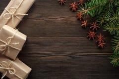 在木背景的圣诞节构成与树、杉木锥体、八角和纸板箱 图库摄影