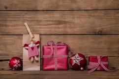 在木背景的圣诞节礼物与天使和红色白色 免版税库存图片