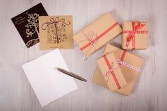 在木背景的圣诞节礼物和白色开放xmas卡片 库存图片
