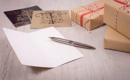 在木背景的圣诞节礼物和白色开放xmas卡片 库存照片