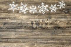 在木背景的圣诞节装饰品白色雪花 免版税库存图片