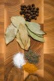 在木背景的基本的香料和草本静物画:黑pe 免版税库存照片