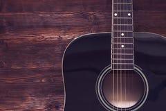 在木背景的声学吉他 免版税库存照片