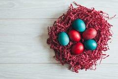 在木背景的复活节彩蛋在巢 免版税库存照片
