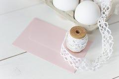 在木背景的复活节彩蛋与桃红色信封 免版税库存图片