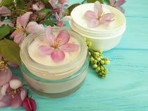 在木背景的奶油色化妆润湿的再生产品秀丽木兰花 免版税库存照片